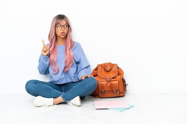Молодой студент смешанной расы женщина с розовыми волосами сидит на полу на белом фоне, думая об идее, указывая пальцем вверх