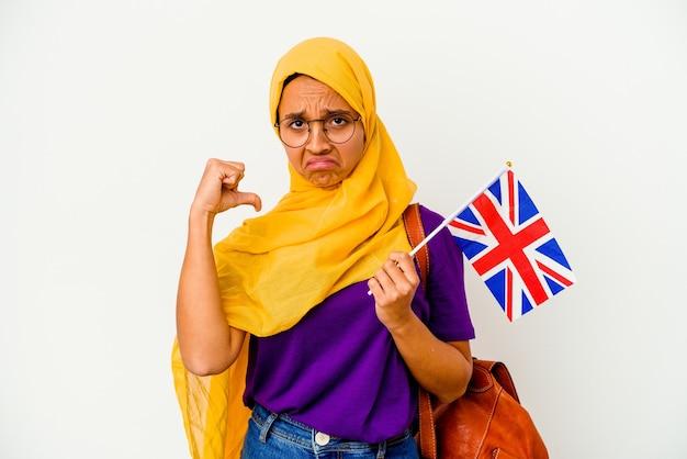 白い背景に隔離された若い学生のイスラム教徒の女性は、誇りと自信を持って、従うべき例を感じます。