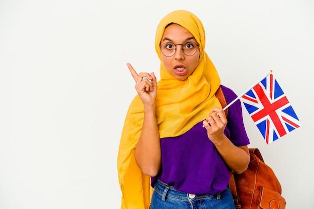 측면을 가리키는 흰 벽에 고립 된 젊은 학생 무슬림 여성