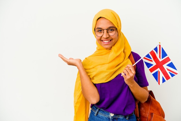 손바닥에 복사 공간을 표시 하 고 허리에 다른 손을 잡고 흰 벽에 고립 된 젊은 학생 무슬림 여성.