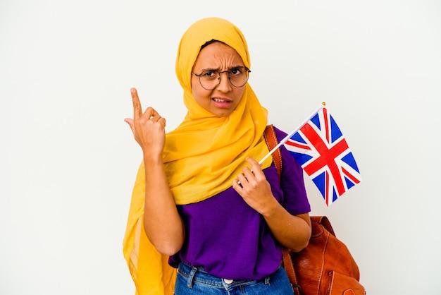 집게 손가락으로 실망 제스처를 보여주는 흰 벽에 고립 된 젊은 학생 무슬림 여성.