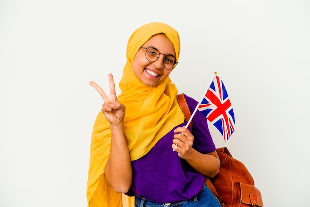 指で2番目を示す白い壁に分離された若い学生のイスラム教徒の女性