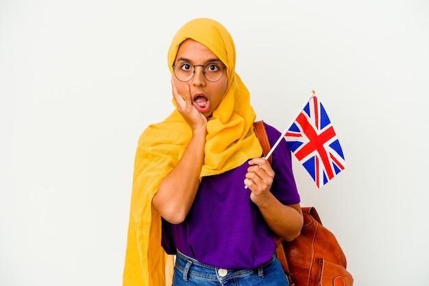 白い壁に隔離された若い学生のイスラム教徒の女性は驚いてショックを受けました。