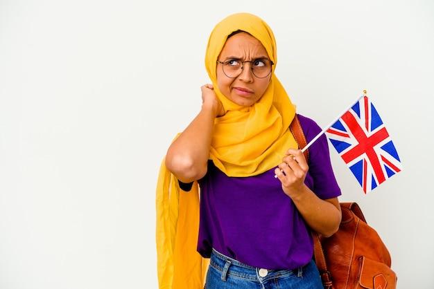 頭の後ろに触れて、考えて、選択をしている白い壁に孤立した若い学生のイスラム教徒の女性。