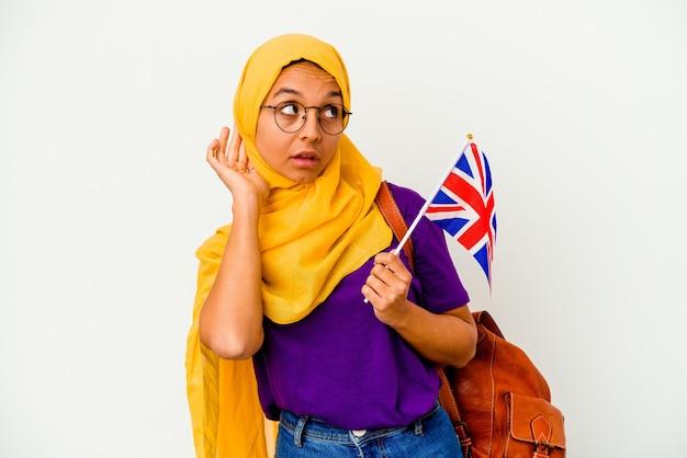 Молодая мусульманская женщина студента изолированная на белой стене пытается слушать сплетню.