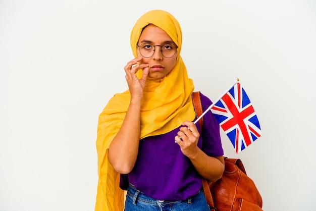 비밀을 유지하는 입술에 손가락으로 흰 벽에 고립 된 젊은 학생 무슬림 여성.