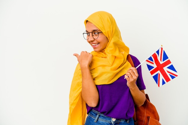 Young student muslim woman isolated on white background points with thumb finger away, laughing and carefree.