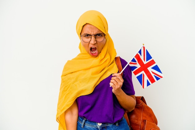 Young student muslim woman isolated on white wall screaming very angry and aggressive.