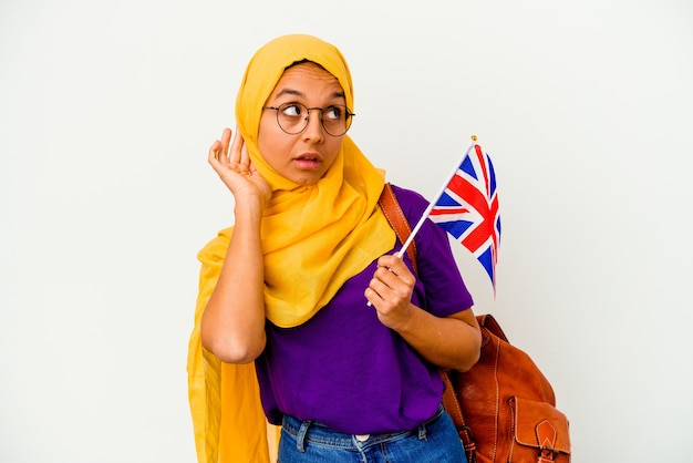 Young student muslim woman isolated on white wall trying to listening a gossip.