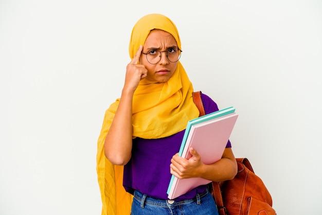 Молодой студент мусульманской женщины в хиджабе, изолированные на белом фоне, указывая храм пальцем, думая, сосредоточился на задаче.