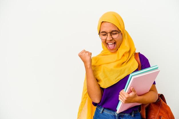 勝利、勝者の概念の後に拳を上げる白い背景で隔離のヒジャーブを身に着けている若い学生のイスラム教徒の女性。