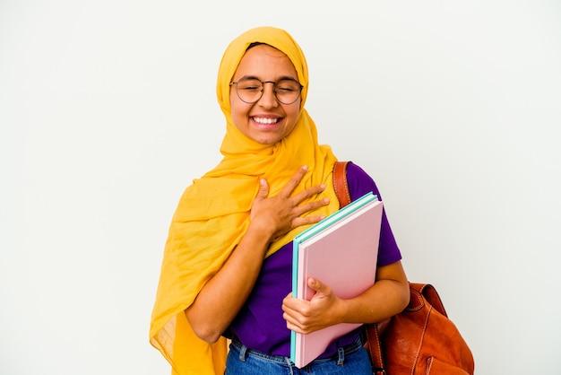 Молодой студент-мусульманка в хиджабе, изолированном на белой стене, громко смеется, держа руку на груди.