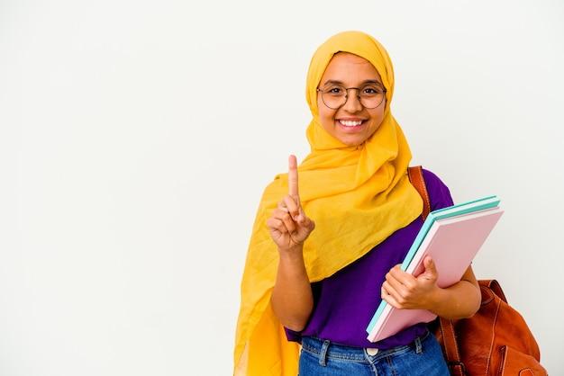 손가락으로 번호 하나를 보여주는 흰 벽에 고립 된 hijab를 입고 젊은 학생 무슬림 여성.