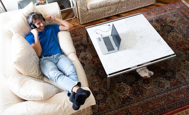 現代のライフスタイルを持つラップトップコンピューターの若者と音楽を聴いてソファで若い学生