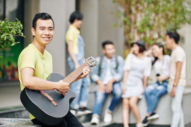 若い学生がギターを弾く