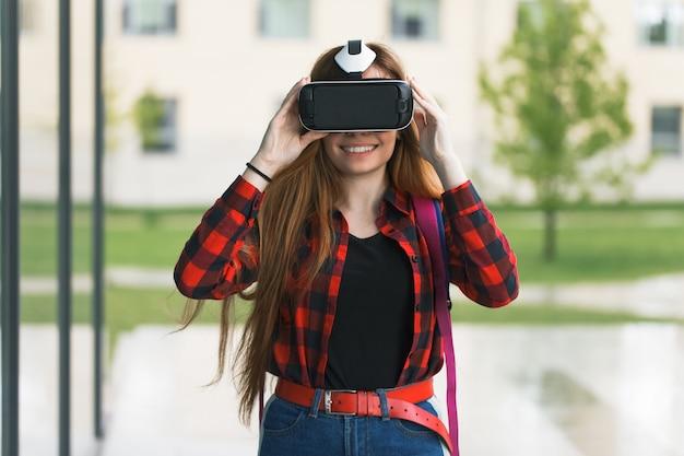 若い学生が仮想現実の眼鏡で遊ぶ