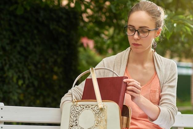 Молодая студентка кладет свои книги в белый пакет, сидя на белой деревянной скамейке.