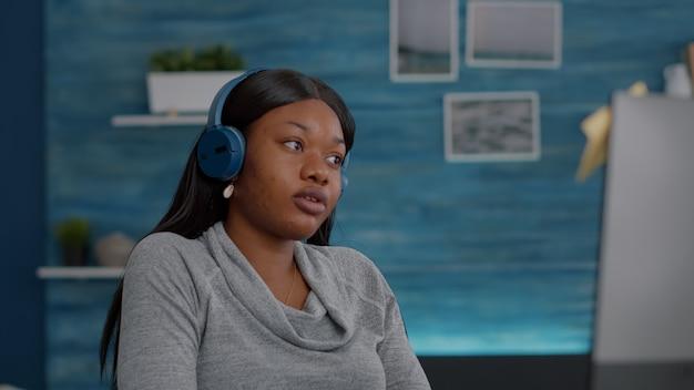 大学のプラットフォームを使用してオンラインコースを検索し、自宅から離れた場所で作業しながら音楽を楽しんでいるヘッドフォンを置く若い学生