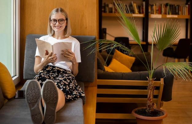 Молодой студент читает книгу в библиотеке