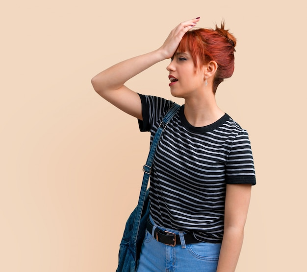 Young student redhead girl intending to realizes the solution on ocher background.