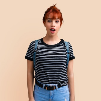 Young student redhead girl with surprise and shocked facial expression on ocher.
