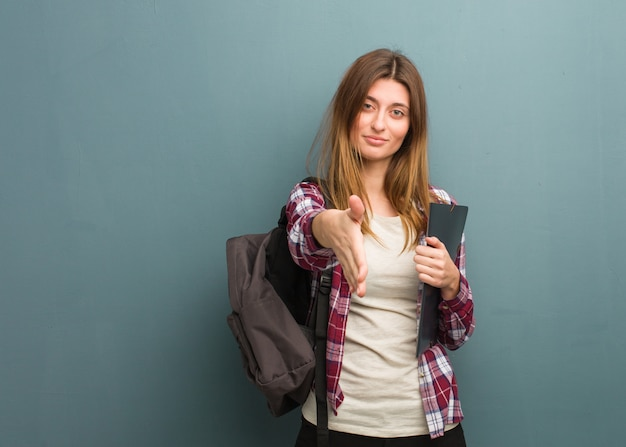 Young student russian woman reaching out to greet someone