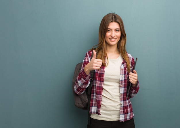 Young student russian woman smiling and raising thumb up