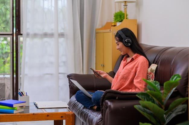 Молодой студент сидит за столом и использует ноутбук