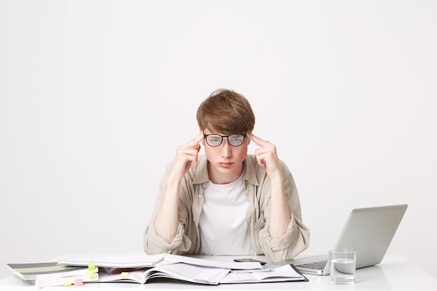 テーブルに座っている若い学生、テーブルに肘を置く
