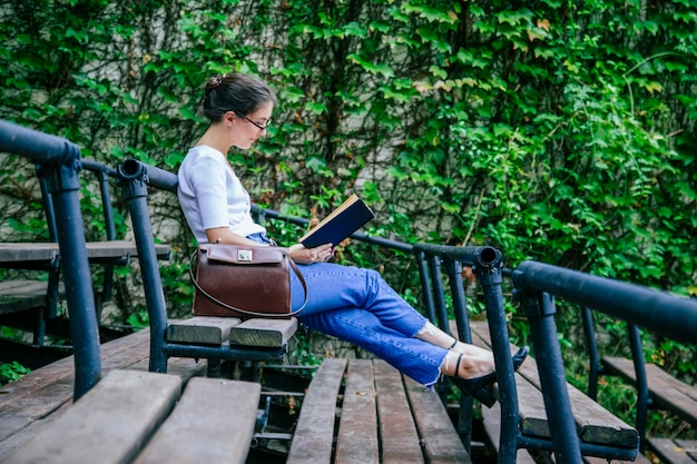 Young student sitting on the campus bench learning with books