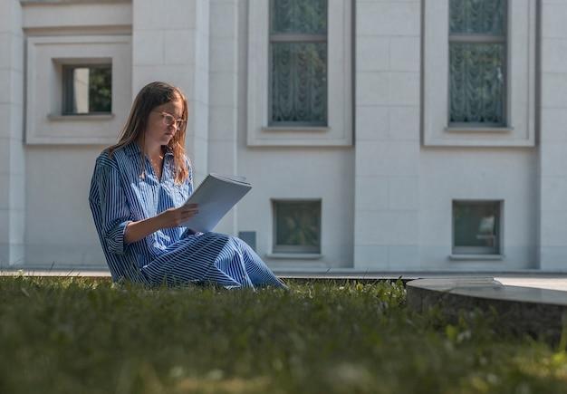 Молодой студент сидит на траве возле здания университета, изучает и читает с академической литературой ...