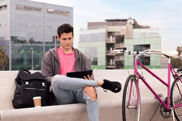 태블릿을 사용하여 야외에 앉아 있는 젊은 학생