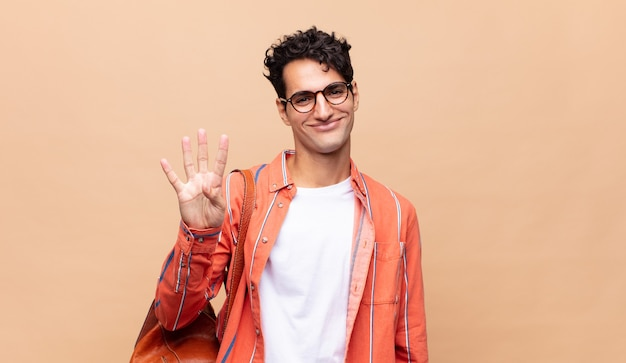 미소하고 친절하게 보이는 젊은 학생, 앞으로 손으로 4 번 또는 4 번을 보여주는, 카운트 다운