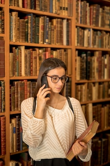 Young student speaking on phone in library