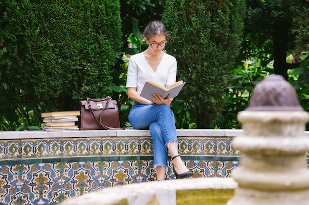 Молодой студент тратит время на чтение для удовольствия