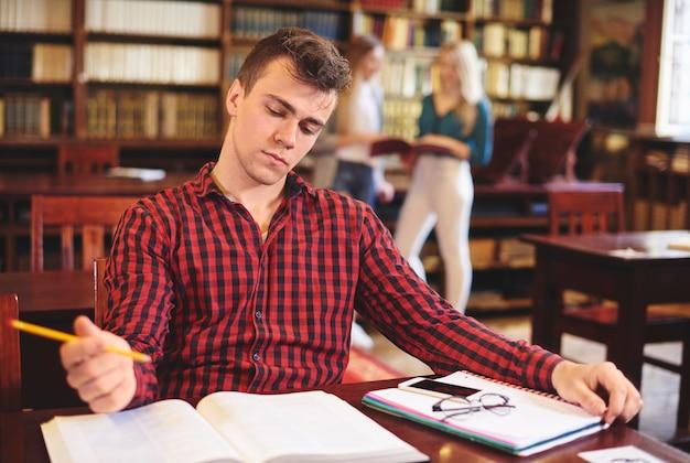 Молодой студент учится в библиотеке