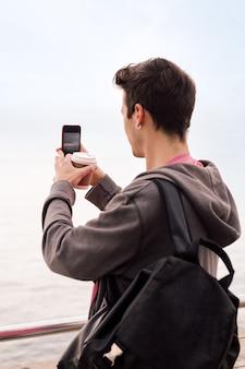 携帯電話で写真を撮る若い学生