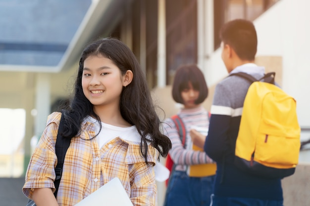 Young student teenager girl high school student carrying schoolbag holding notebooks with friends in background