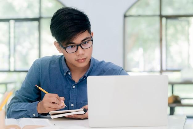 オンラインで勉強しているコンピュータを使用している若い学生。教育とオンライン学習。