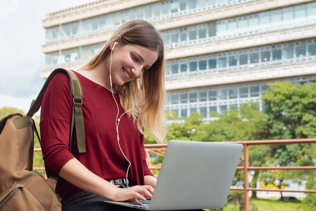 야외에서 노트북을 사용하는 젊은 학생.