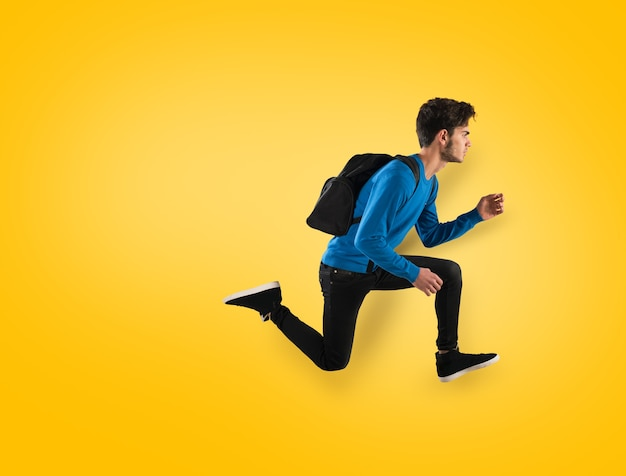 Young student with backpack run on yellow background