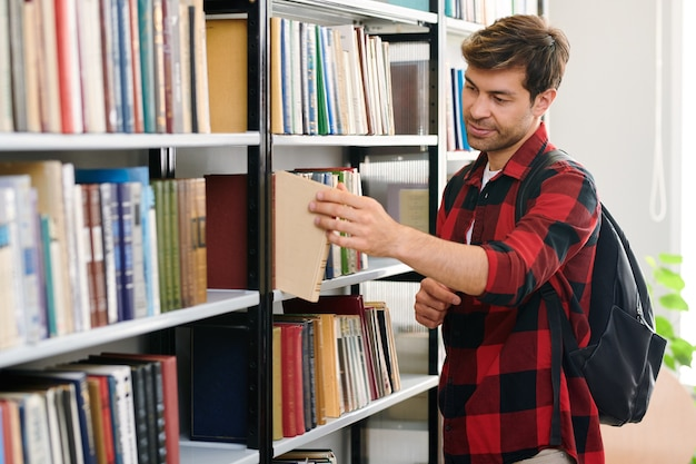 Молодой студент с рюкзаком берет одну из книг с полки во время посещения библиотеки колледжа