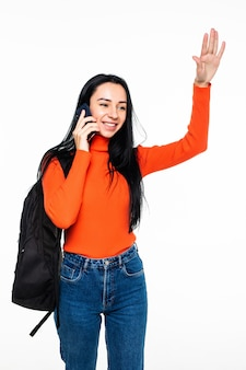 Giovane studente con il telefono di conversazione della borsa ed onda con le mani isolate sulla parete bianca