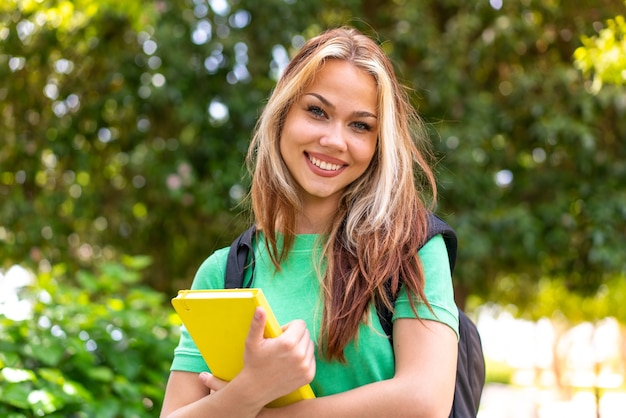 Молодая женщина студента на открытом воздухе держа тетрадь