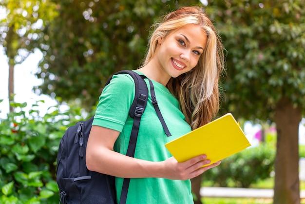 야외에서 노트북을 들고 있는 젊은 학생 여자