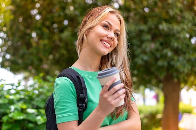 テイクアウトコーヒーを保持している屋外で若い学生女性