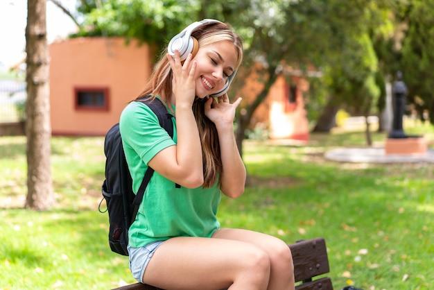 Молодой студент женщина на открытом воздухе, слушать музыку