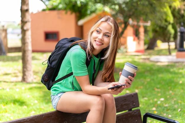 Молодая женщина-студент на открытом воздухе с помощью мобильного телефона и кофе на вынос