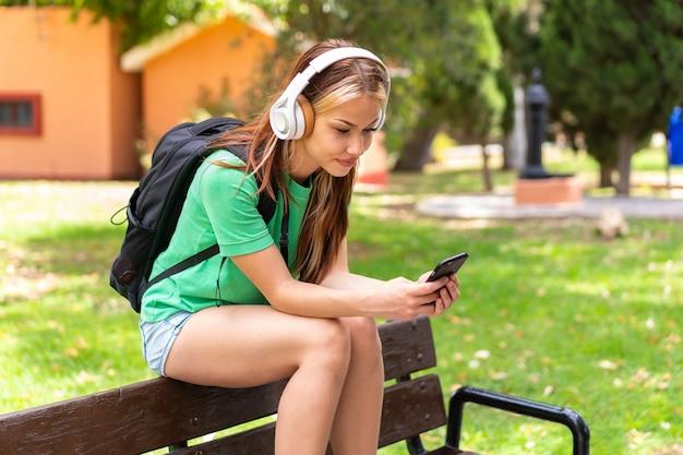 Молодая женщина студента на открытом воздухе с помощью мобильного телефона