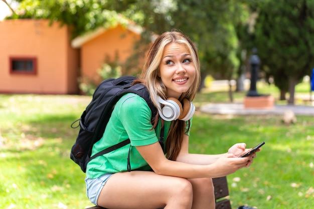 携帯電話を使用して屋外で若い学生女性